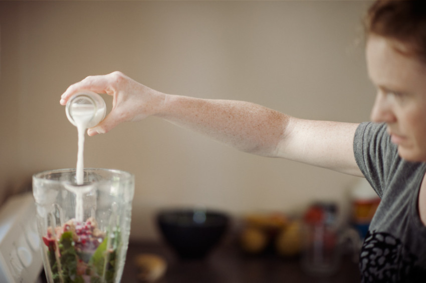 A female adds some non-dairy milk to a blender for a Green Smoothie