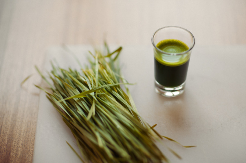 Loose wheat grass sits beside a shot of wheat grass on a chopping board