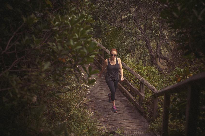 Naturopath Lisa Fitzgibbon walking through the bush on a wooden path in Waiheke Island