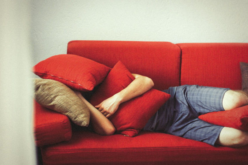 A man lies on a couch hiding his head with cushions as he is experiencing severe untreated food intolerance