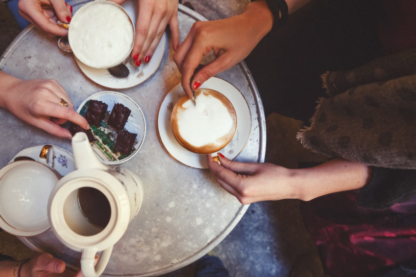 A close-up of three woman drinking coffee around a small table