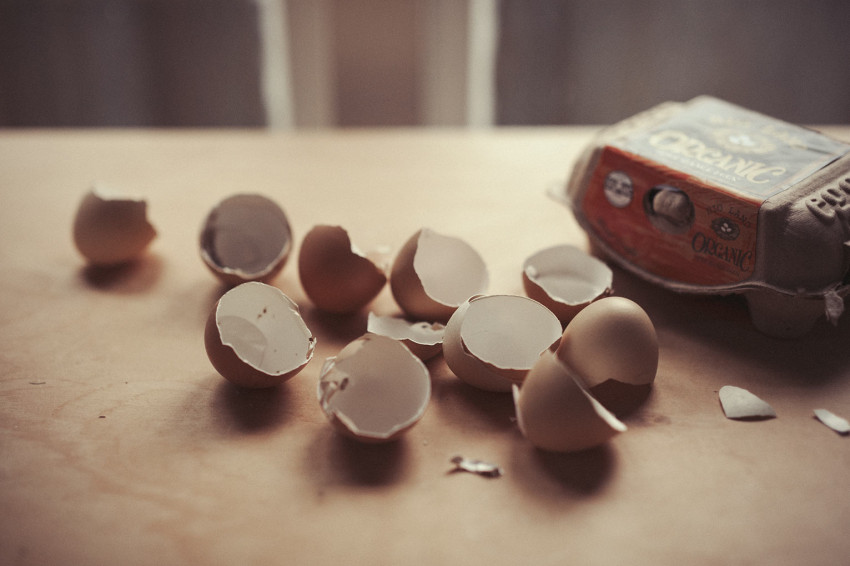 A number of egg shells are displayed next to their carton on a table-top