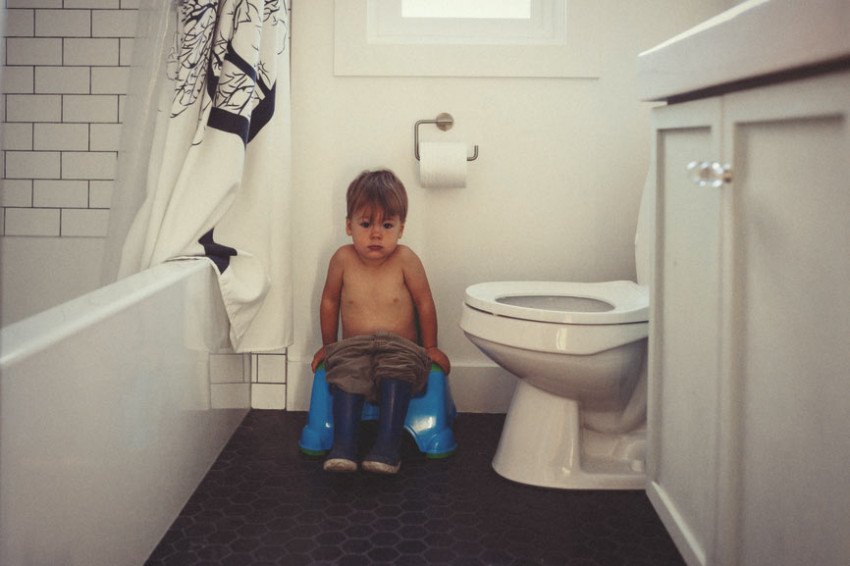 A little boy sits on a potty in a bathroom to indicate healthy bowel motions