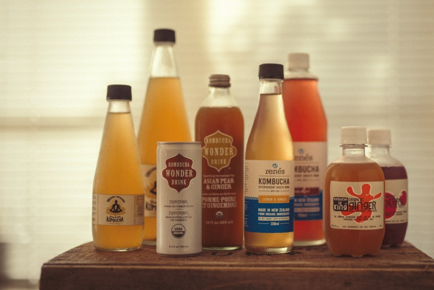 An array of different brands of Kombucha sit on a box