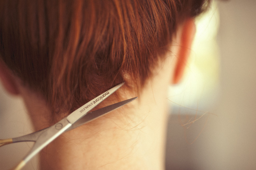 Naturopath Lisa Fitzgibbon displays her red hair and uses scissors to indicate where to take the sample from