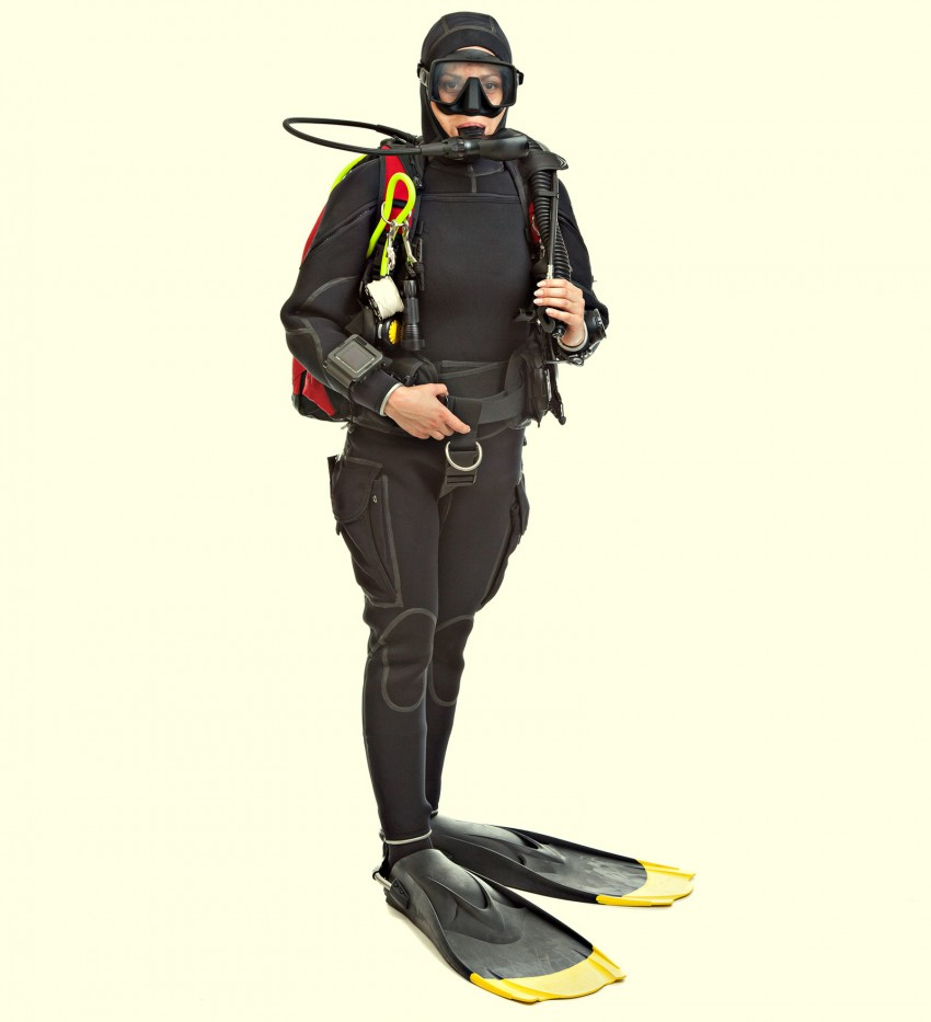 A scuba diver in full entire standing on land