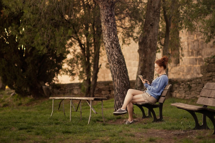 Naturopath Lisa Fitzgibbon feeling healthy sitting on a park bench reading in the South of France