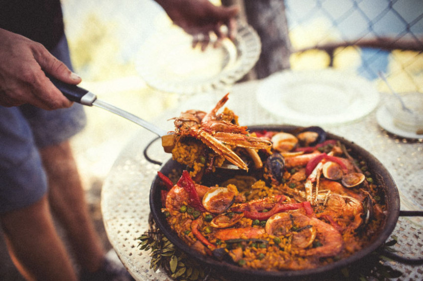 A pan-full of delicious seafood has just been cooked and a man is about to serve it up