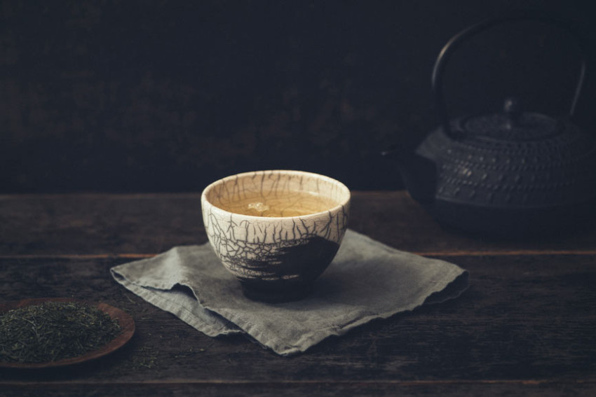 A single cup of Green Tea sits on a cloth napkin to indicate that antioxidants are important