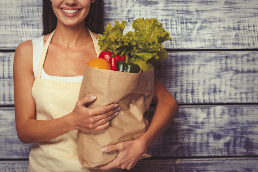 A young woman stands with a single brown bag's worth of wholefoods to indicate simple healthy meals