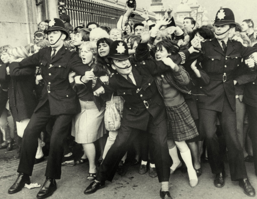 A mob of women from the mid 1900s being held back by London bobbies to symbolise health food trends