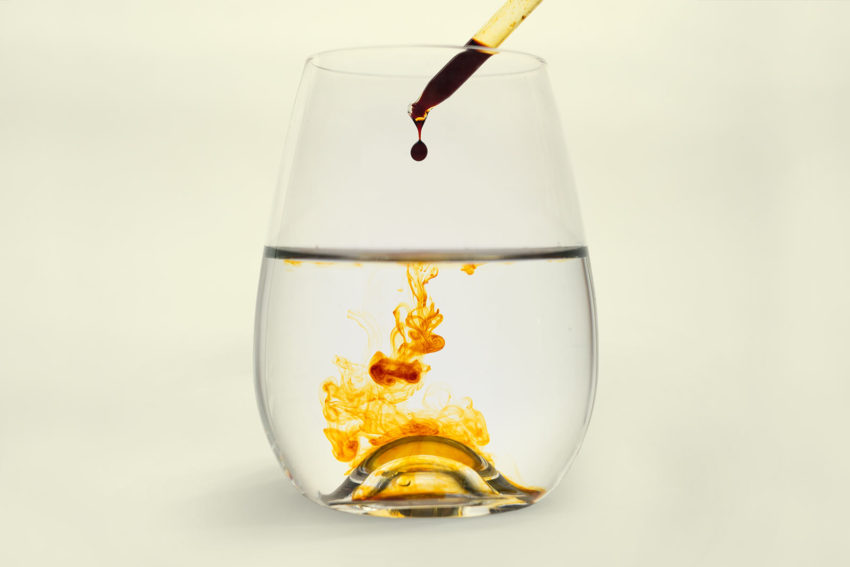 Iodine solution being dropped into a wine glass of water