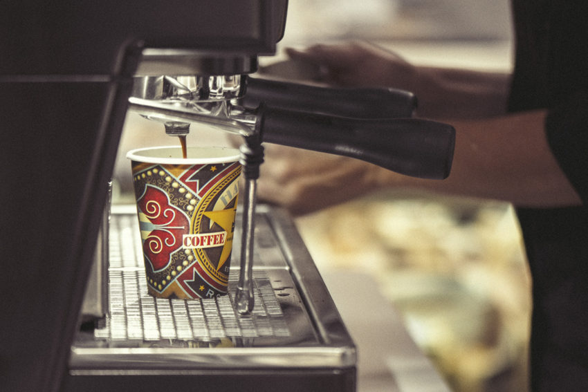 An espresso machine drizzles coffee into a colourful paper cup