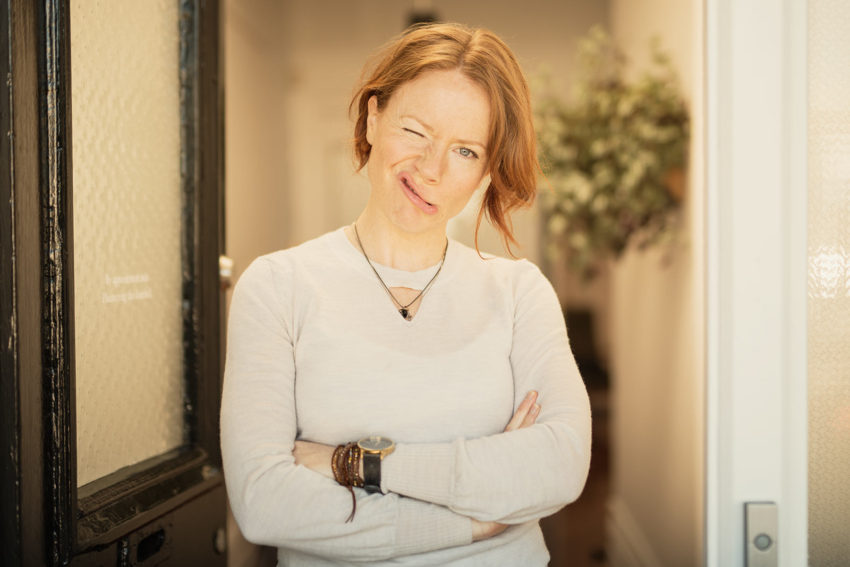Naturopath Lisa Fitzgibbon standing pulling faces in her practice's doorway