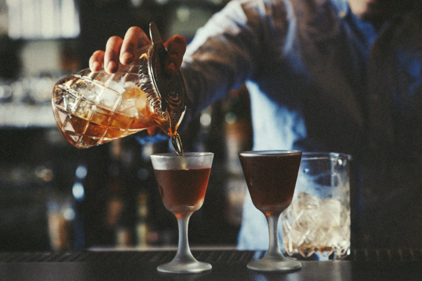 A bartender fills some elegant drinking vessels with some premium spirits