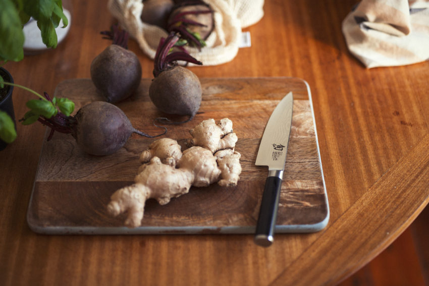 Beetroot and ginger lie on a chopping board ready to be cut with a knife