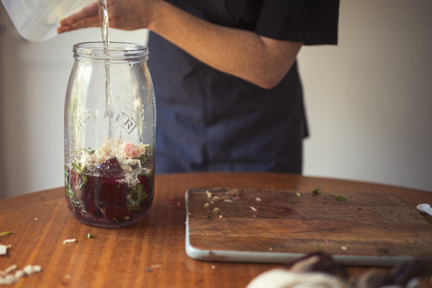 Naturopath Lisa Fitzgibbon fills a large jar with the ingredients for making beetroot Kvass