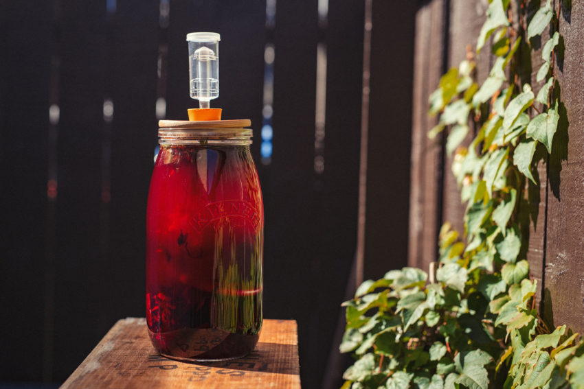 A large jar of fermenting beetroot Kvass sits on a table outside