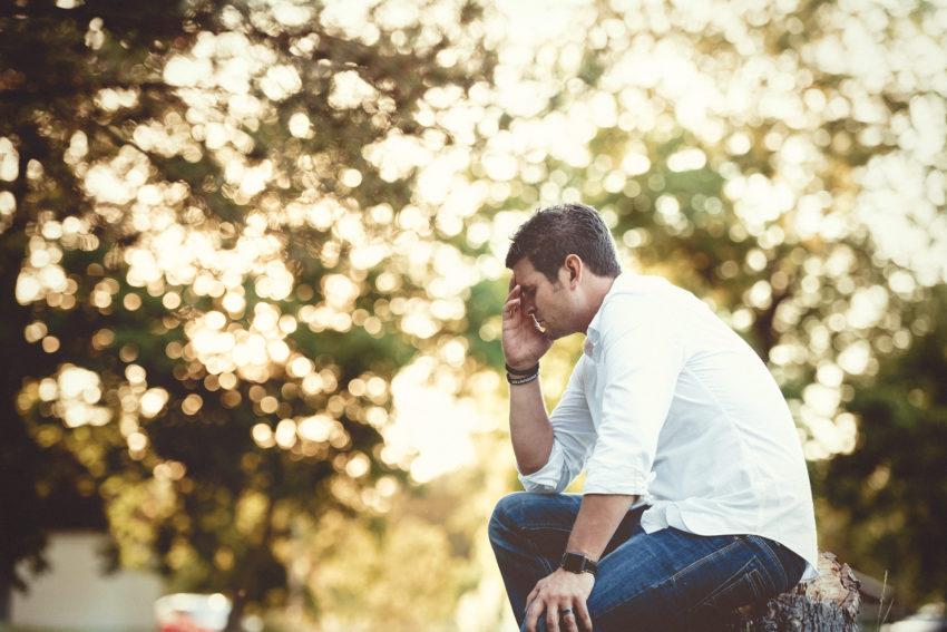 A young man suffering from chronic stress is sat down outside holding his face in his hand