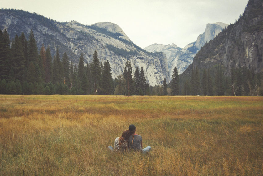 A young couple in a healthy romantic relationship sit on the ground touching admiring the view