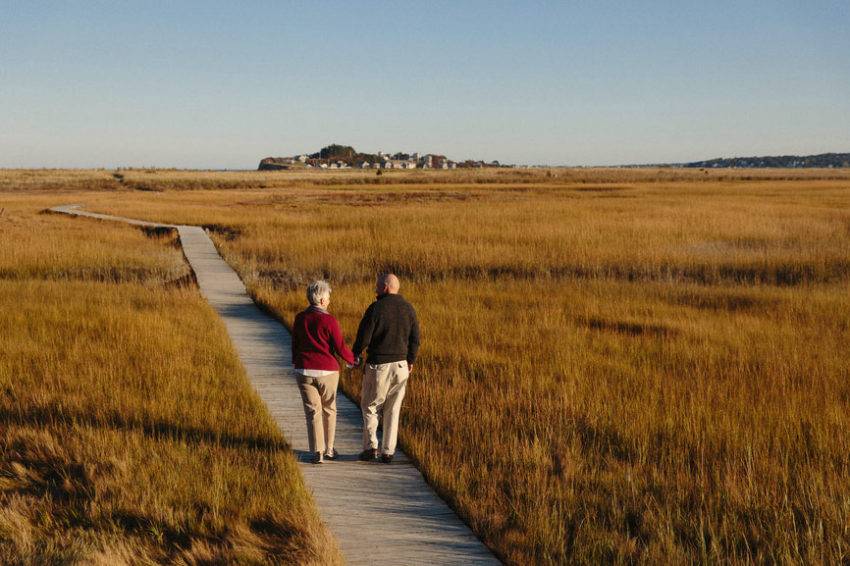 An elderly couple hold hands as they walk up a path amongst dry grass