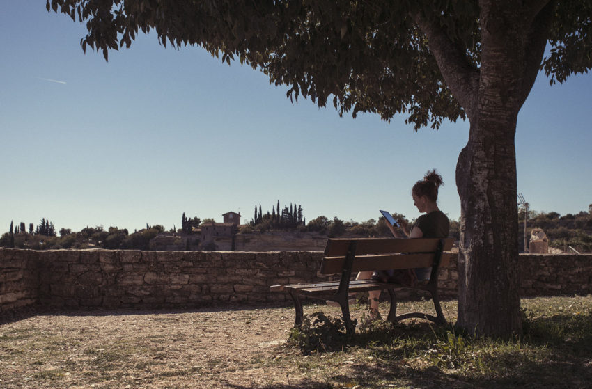 Naturopath Lisa Fitzgibbon reading under a tree in a village in the south of France