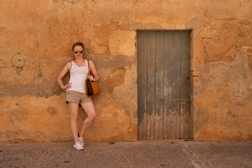 Naturopath, Lisa Fitzgibbon, looking sassy and leaning on a brick wall in Mallorca