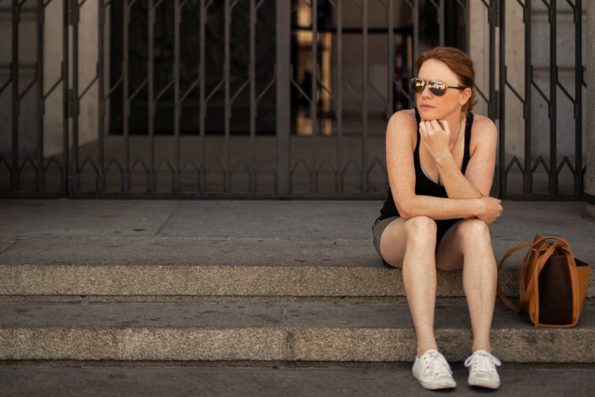 Naturopath Lisa Fitzgibbon sits on the steps of a building in Madrid she used to follow a vegetarian diet