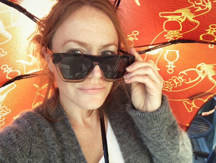 Naturopath, Lisa Fitzgibbon under a Karen Walker Umbrella wearing oversized sunglasses