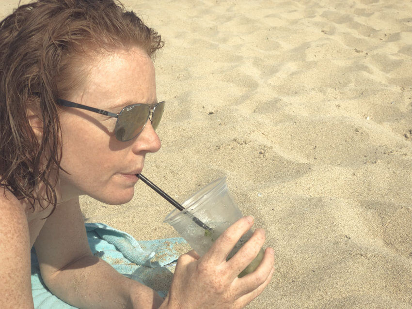 Naturopath, Lisa Fitzgibbon, laying on a beach in Mallorca sipping a Mojito