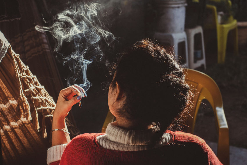 A young woman smokes Marijuana with her back to the camera