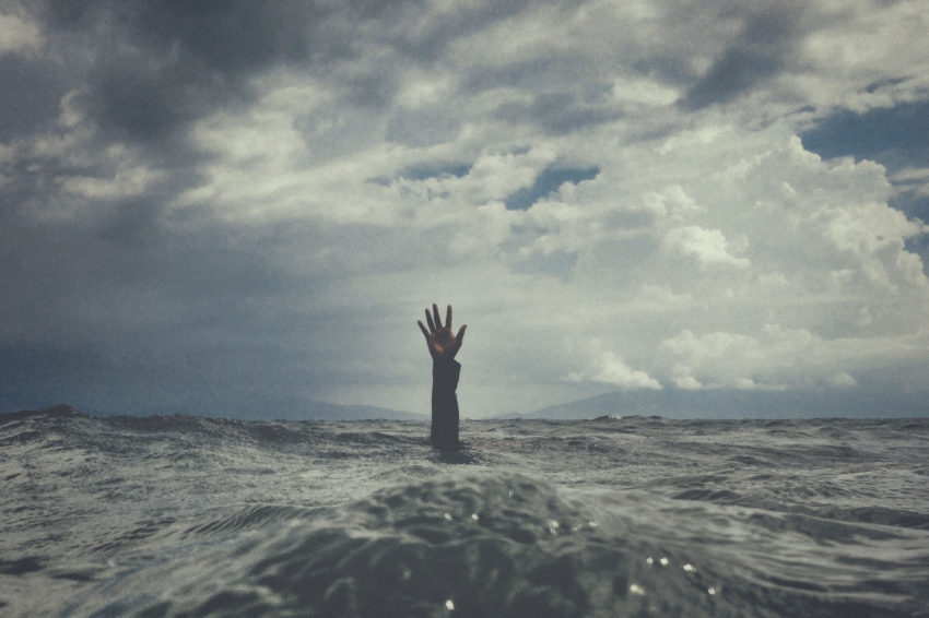 A hand with open palm desperately reaches high out of the ocean to portray living with anxiety