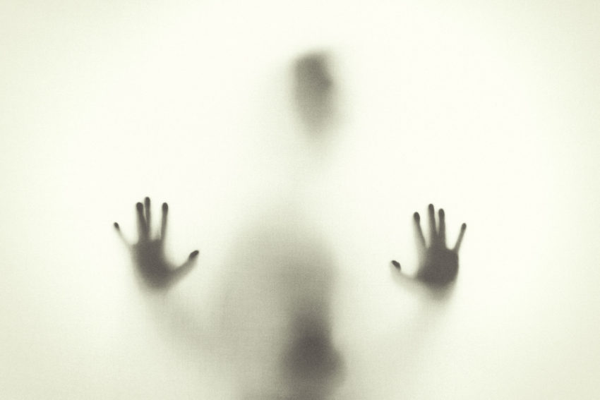 A shadow of a person with hands pressed up to a clear screen to portray living with anxiety