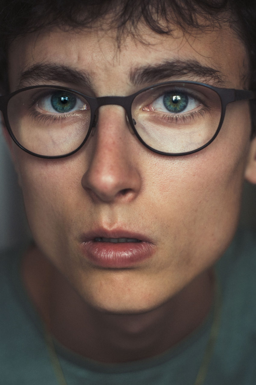 Androgynous person wearing reading glasses has healthy limbal rings of the eyes