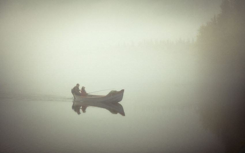 Two fishermen occupy a lone small boat on a misty morning
