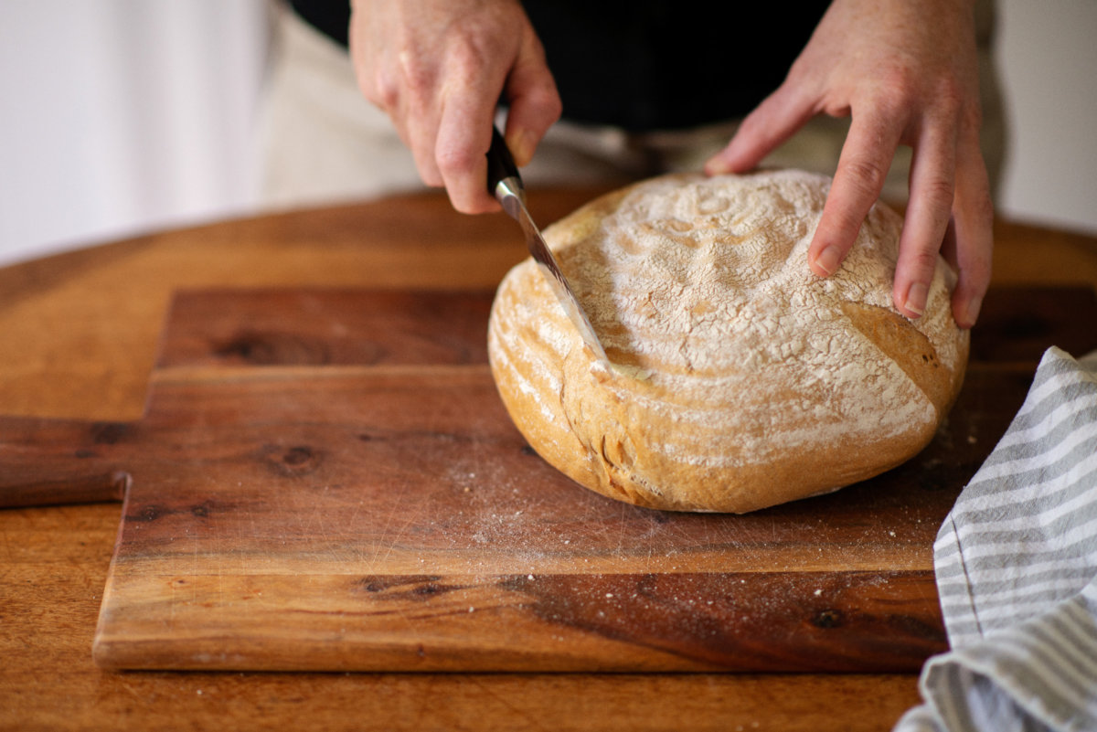 San Francisco Sourdough bread is being cut on a chopping board by Naturopath Lisa Fitzgibbon