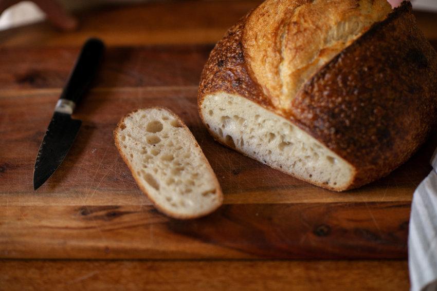 Freshly cut Artisan Sourdough bread and a knife sit on a wooden chopping board